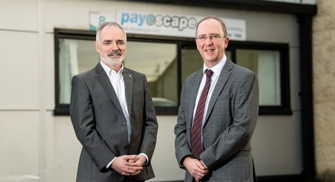 Two men in business attire are standing and smiling into the camera with a sign on a wall behind them for Payescape.