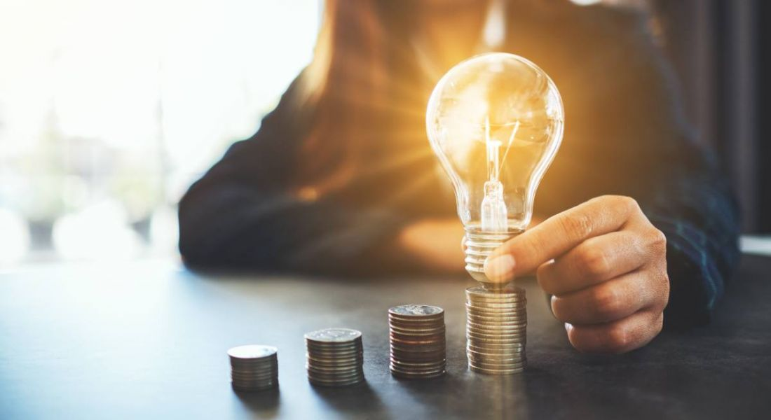 Professional woman holding and putting lightbulb on coins stack on table, representing inspiration in the financial services sector.