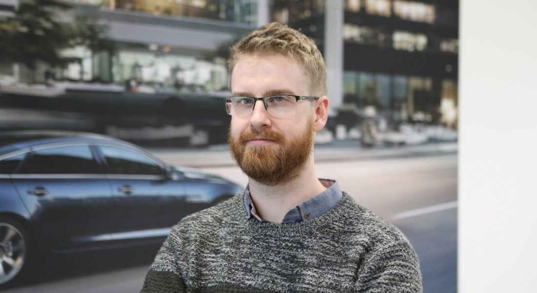 Aaron Hetherington is looking into the camera against a picture of a car on a street at the JLR offices in Shannon.