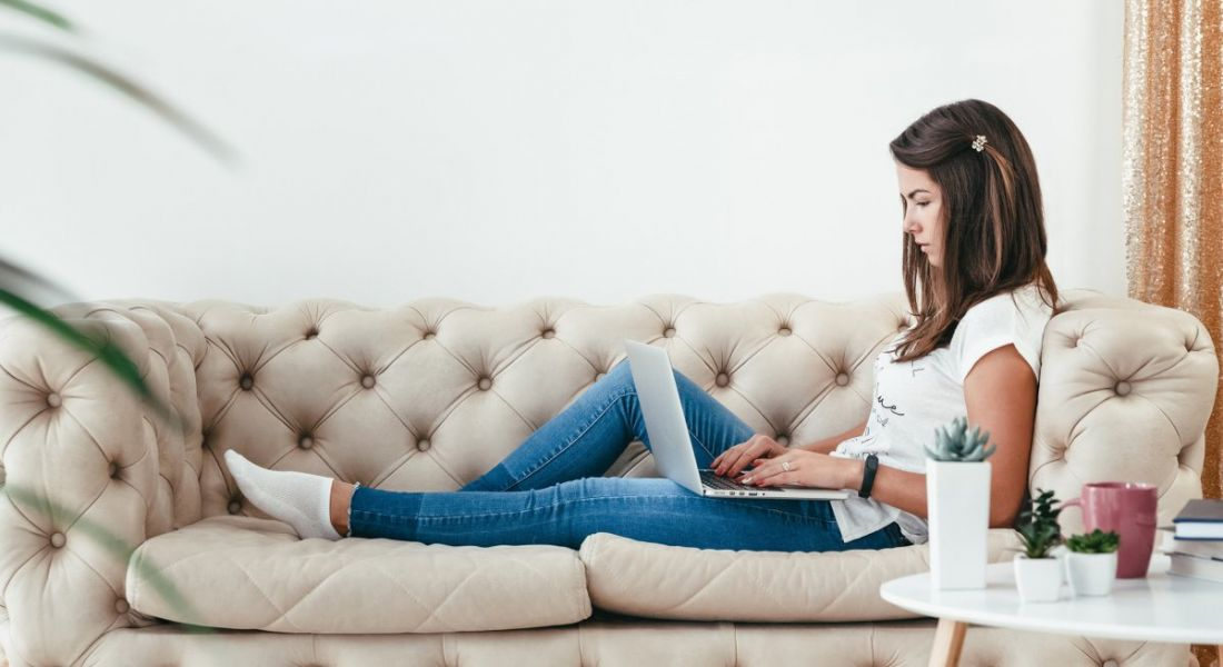 A casually dressed young woman working from home on a laptop, stretched out on a sofa next to a coffee table with a mug and some small potted plants.