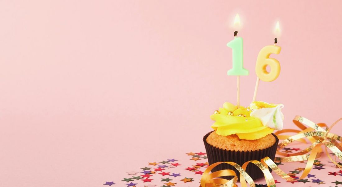 A cupcake with a 16 candle is sitting on a table against a pink background.
