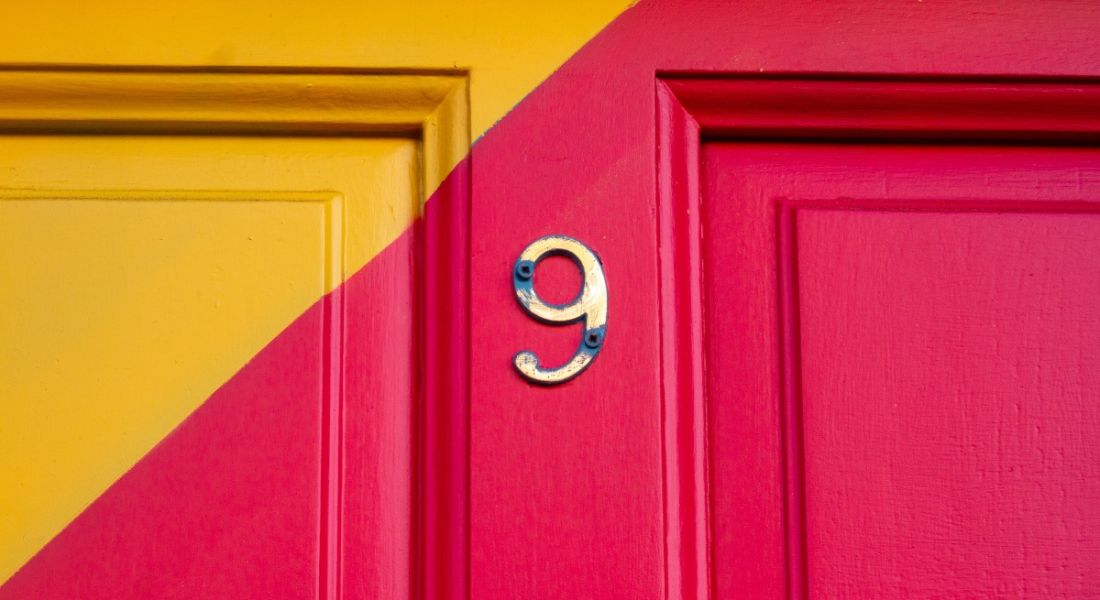 Number 9 on a pink and orange front door.