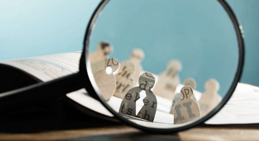 Recruitment or hiring concept with icons of candidates made from paper standing on an open newspaper under a magnifying glass.