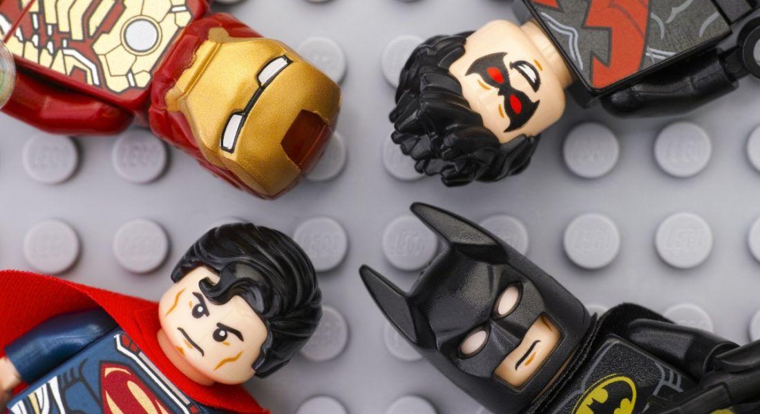 Four Lego superheroes mini-figures on grey Lego baseplate background.