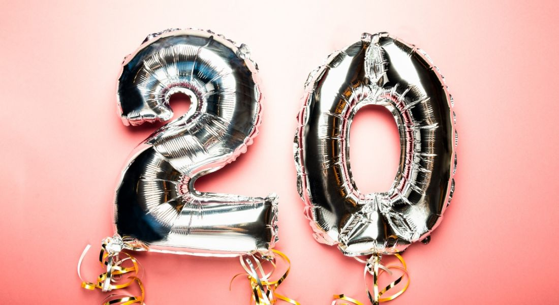 Two inflated silver balloons with curling strings attached on a soft pink background. The balloons read '20'.