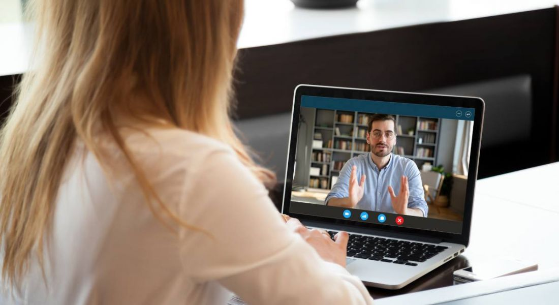 View over shoulder of employer conducting a remote interview using video conferencing technology.