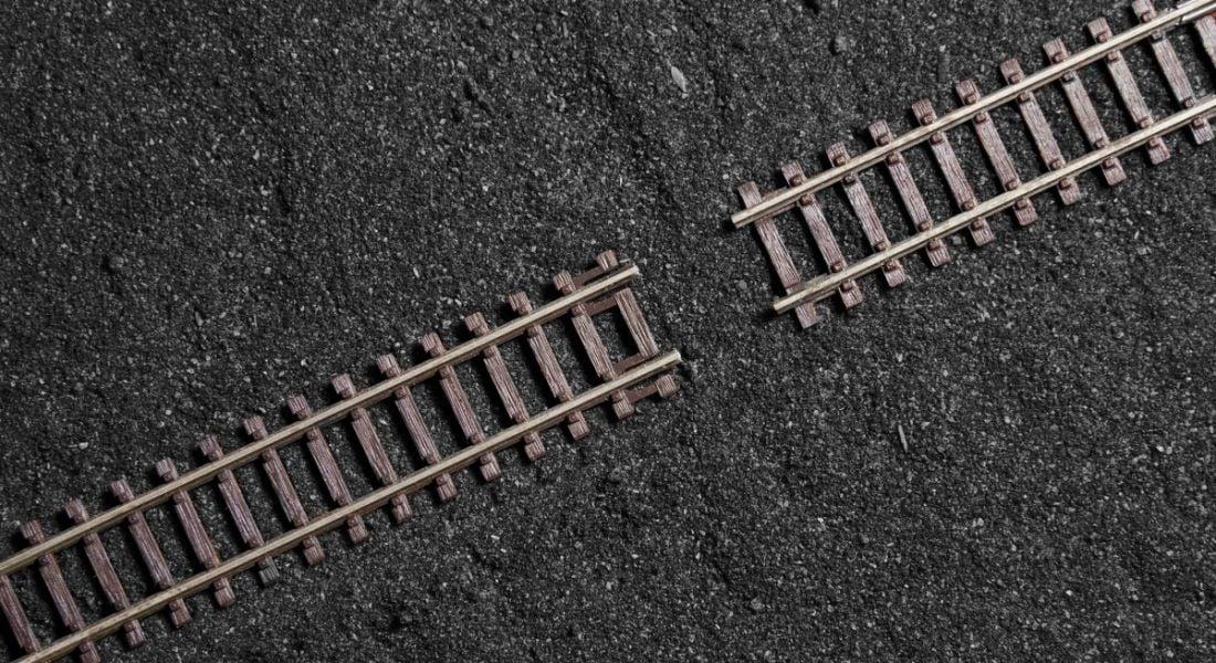 A gap in wooden railway tracks across a dark, gritty surface.