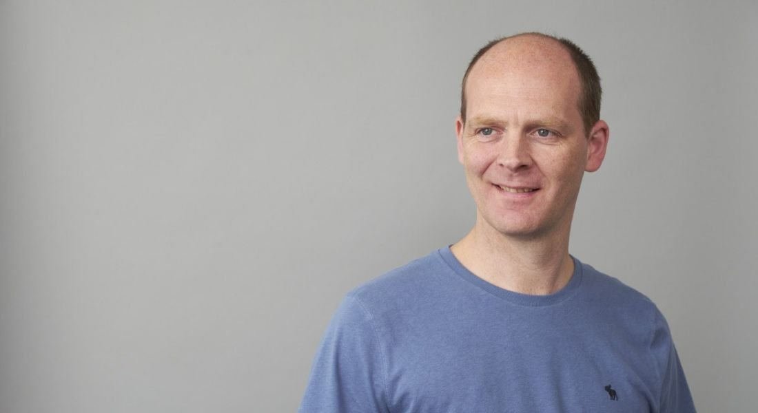 Dave Anderson is wearing a blue T-shirt and standing against a pale backdrop.