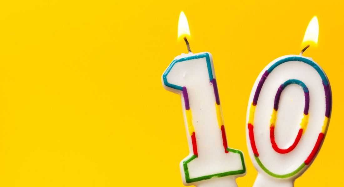 Number 10 birthday celebration candles against a bright yellow background.