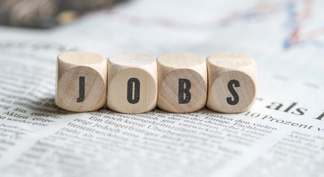 The words jobs is spelled out with wooden blocks sitting on top of a newspaper.
