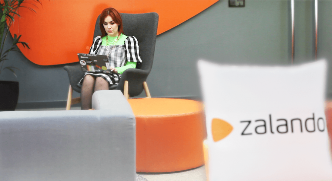 Zara McBrien is sitting on a chair at Zalando Dublin and working on a laptop.