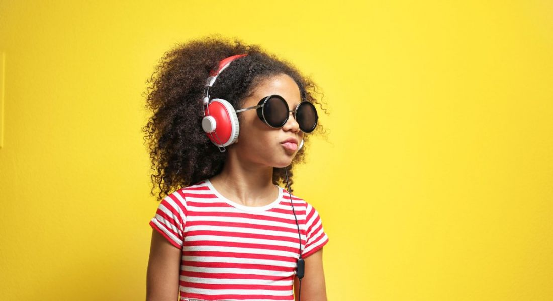 Little girl with headphones listening to music, against a yellow background.