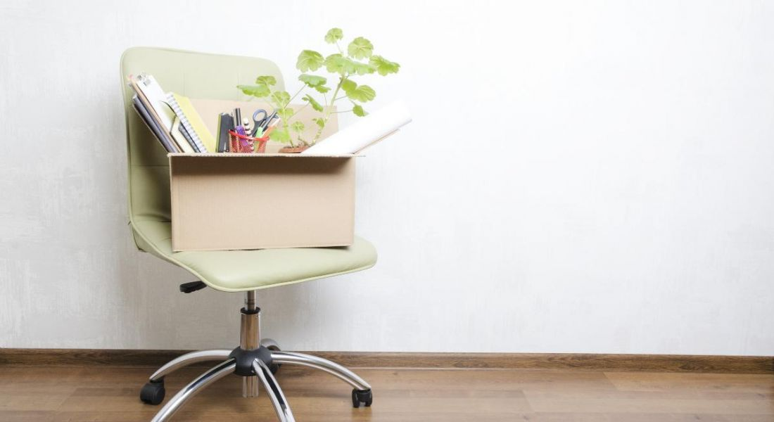 Box with personal items on an office chair, against a white wall.