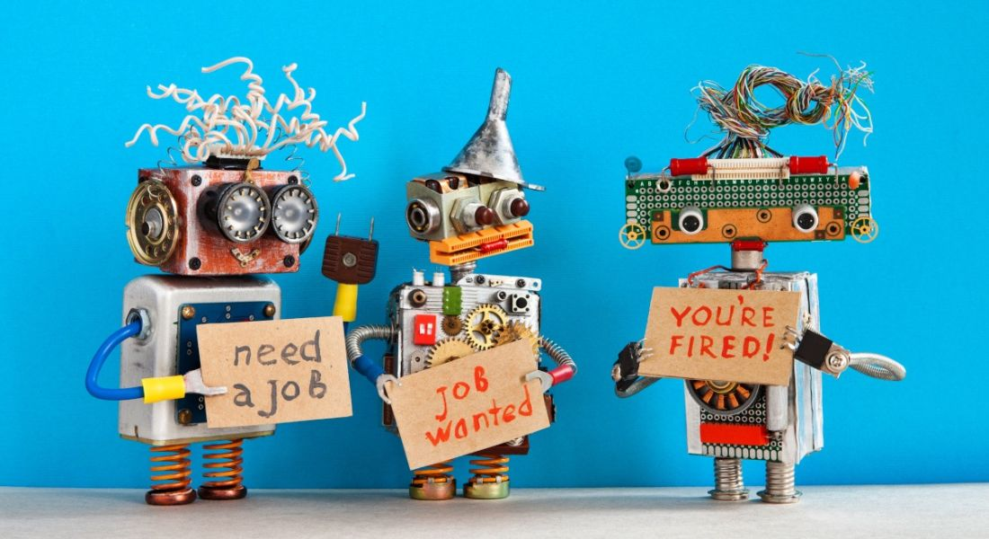 Small toy robots holding signs relating to jobs and recruitment.