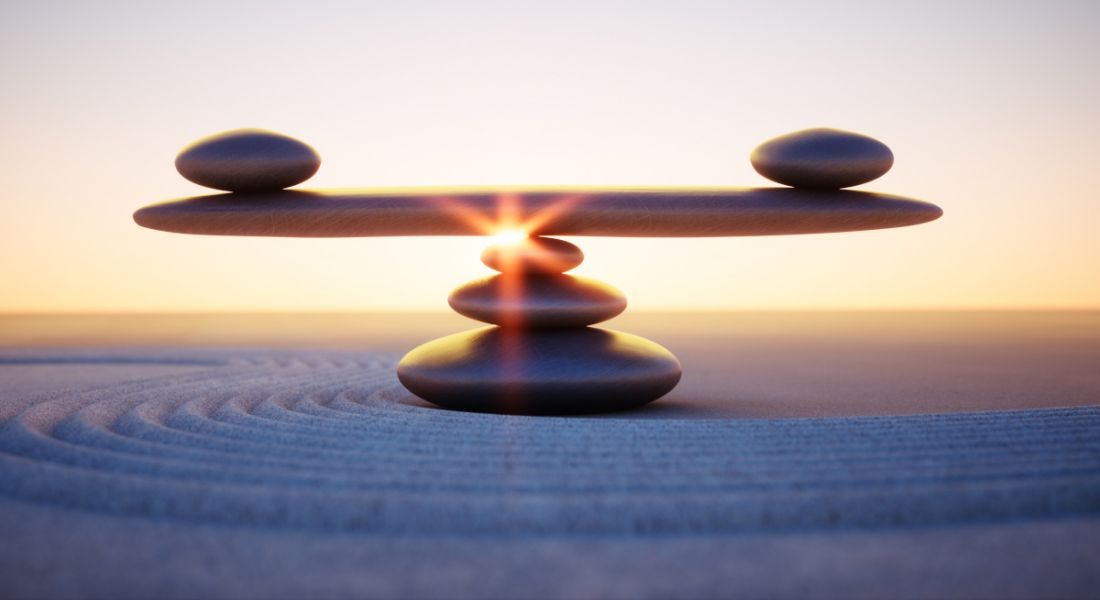 A seesaw made of stones perfectly balanced on a bed of sand against a sunset background.