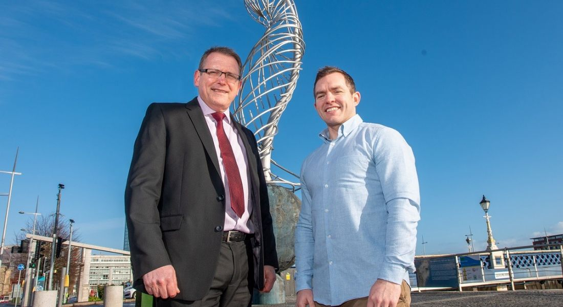 Derek Andrews in a black suit with red tie, and Conor O'Loughlin in a blue shirt and grey chinos, standing in front of a wire statue against a sunny sky.