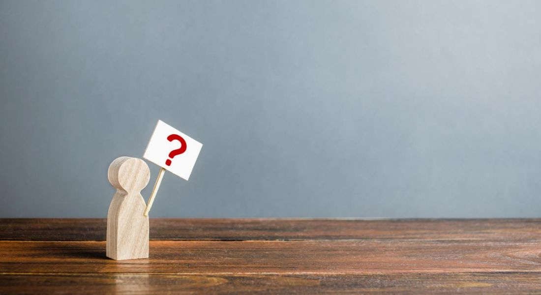A small wooden figurine is holding a poster with a question mark on it.
