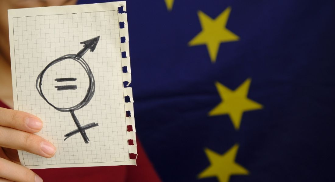 Person holding up a sheet of paper with symbols for gender equality on it, with the EU flag in the background.