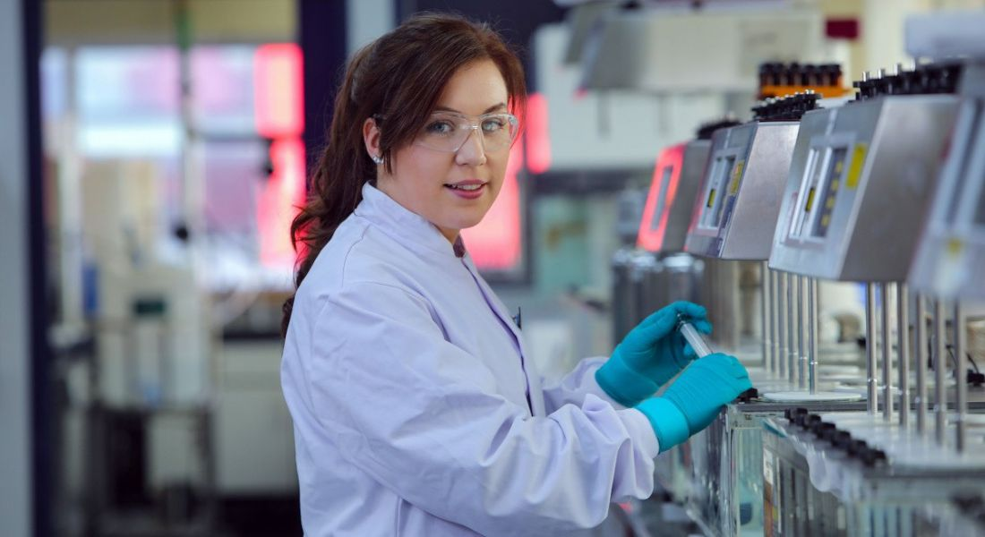 A woman is working in a lab at a station and looking into the camera.
