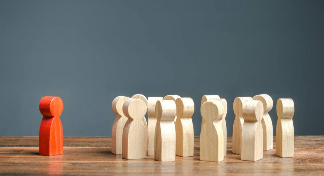 Red wooden figurine stands in front of a group of other wooden figures.