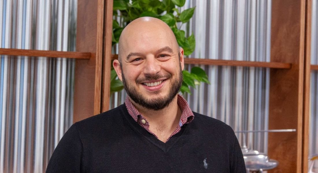 DevOps engineer at Viasat Ireland, Adrian Fachal, is smiling into the camera at the company's Dublin office.