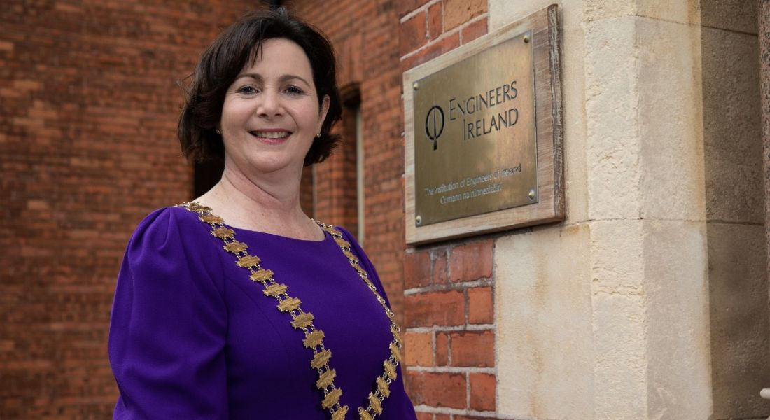 Marguerite Sayers is standing outside of the Engineers Ireland building and wearing a purple dress while smiling into the camera.