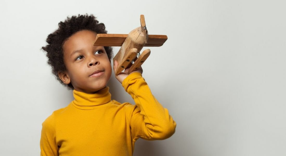A boy in a yellow jumper playing with a wooden plane model.