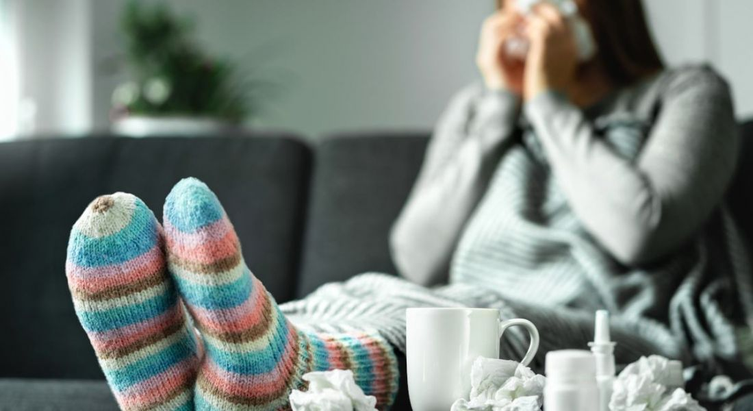 Sick woman with cold sitting on couch at home.
