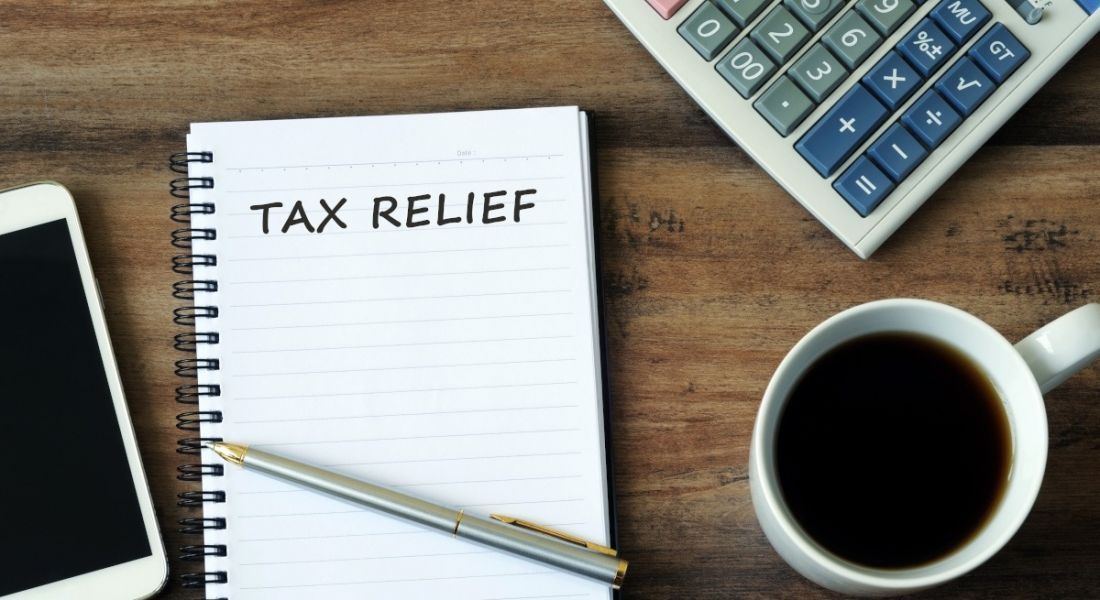 Tax relief written on a notepad with smartphone, pen, coffee and calculator on a wooden table.