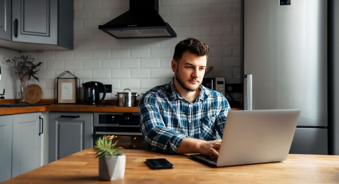 A man with a laptop sits at his kitchen table. You can see kitchen counters and a hob behind him.