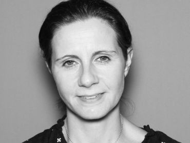 Black-and-white image of Olivia Leonard of Mastercard is smiling into the camera.