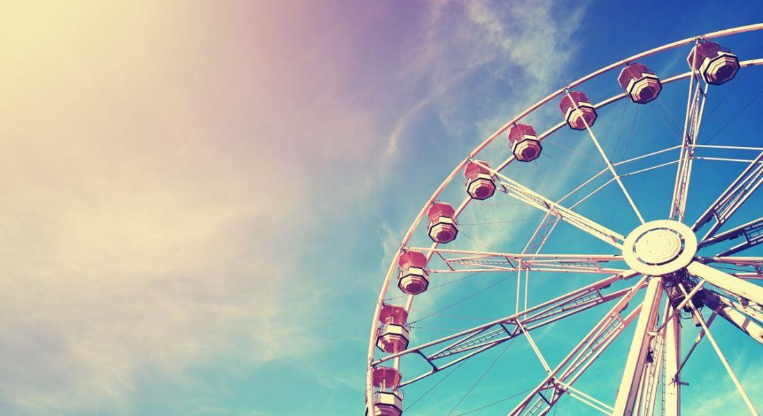 Photo of a ferris wheel against a blue sky, symbolising a hub and spoke model.