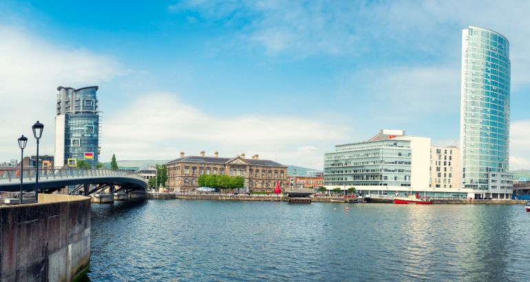 Panoramic view of the river Lagan in Belfast city, with office blocks overlooking the water.