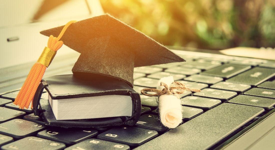 Black graduation cap, leather notebook and diploma on a laptop, symbolising software graduates.