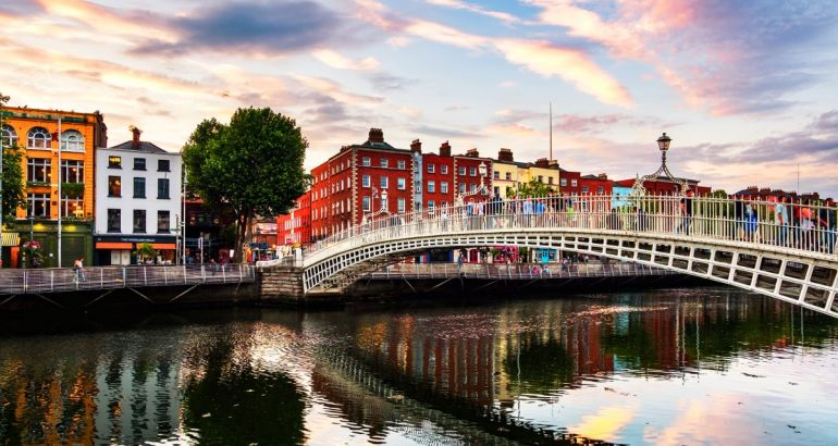 Photo of Ha'penny Bridge in Dublin, Ireland against a bright sky.