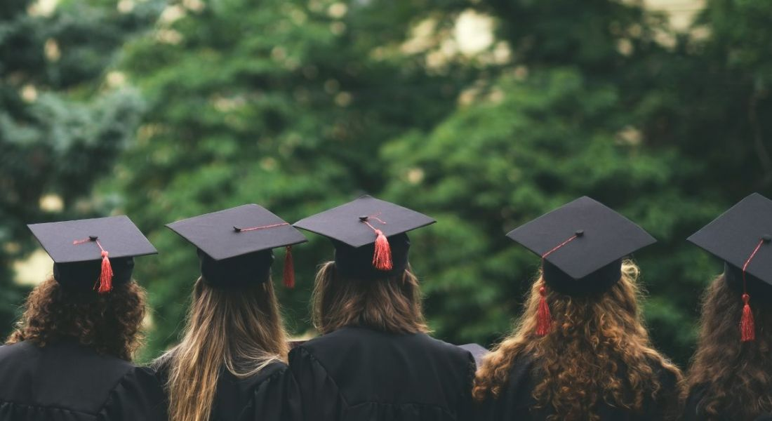 A group of graduates are standing with their backs to the camera in an outdoor setting.
