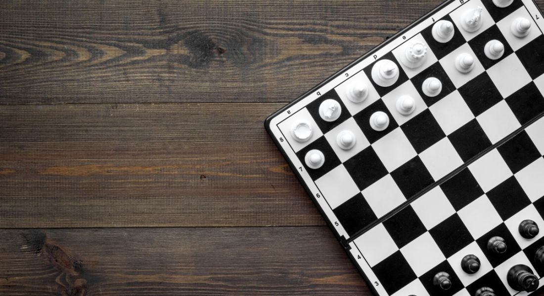 Top-down view of a black and white game of chess on a dark wooden table, symbolising game-based learning.