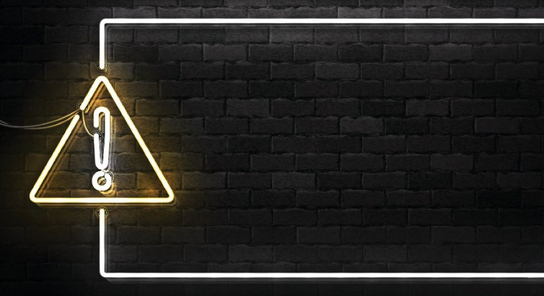 A lit up warning sign against a black brick background.