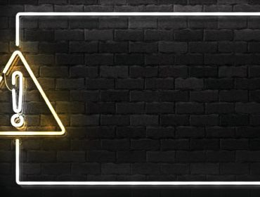 A lit up warning sign against a black brick background.
