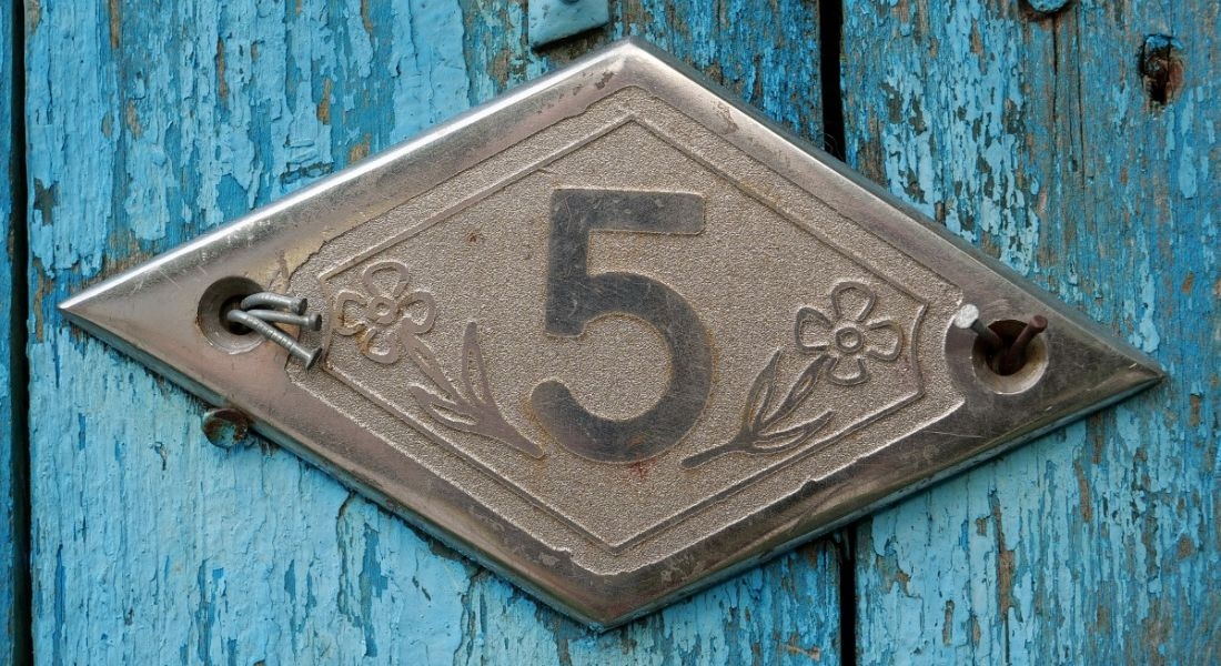 A blue wooden door with a sign reading number five on it.