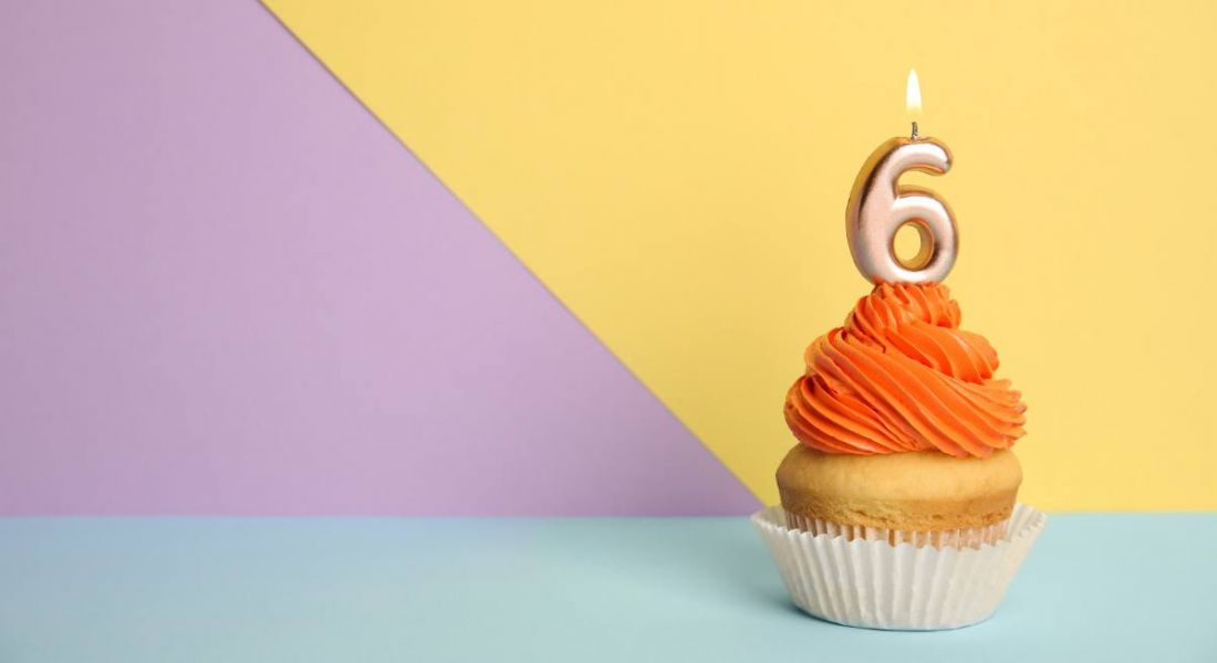 Birthday cupcake with number six candle on a yellow, purple and blue background.