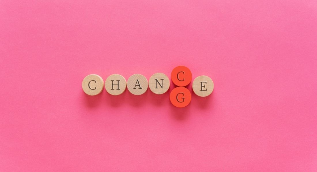 The word 'change' is spelled out on small wooden circles, with the letter G in red being pushed out by the letter C, changing the word to 'chance'.