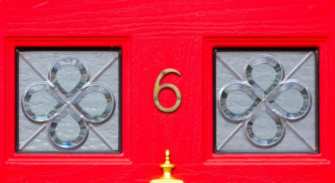 Bright red front door with square windows and a gold number six.