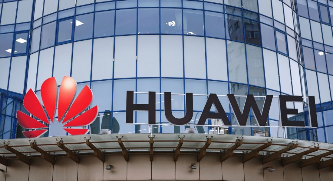Huawei logo above the entrance to a glass office building.