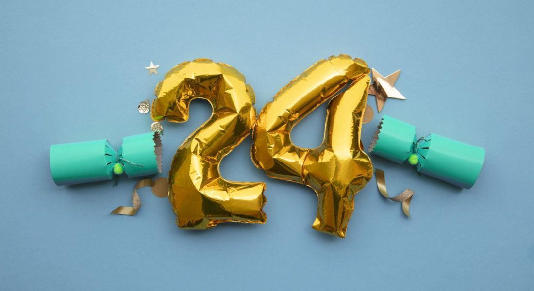 Gold foil number 24 balloons against a blue background.