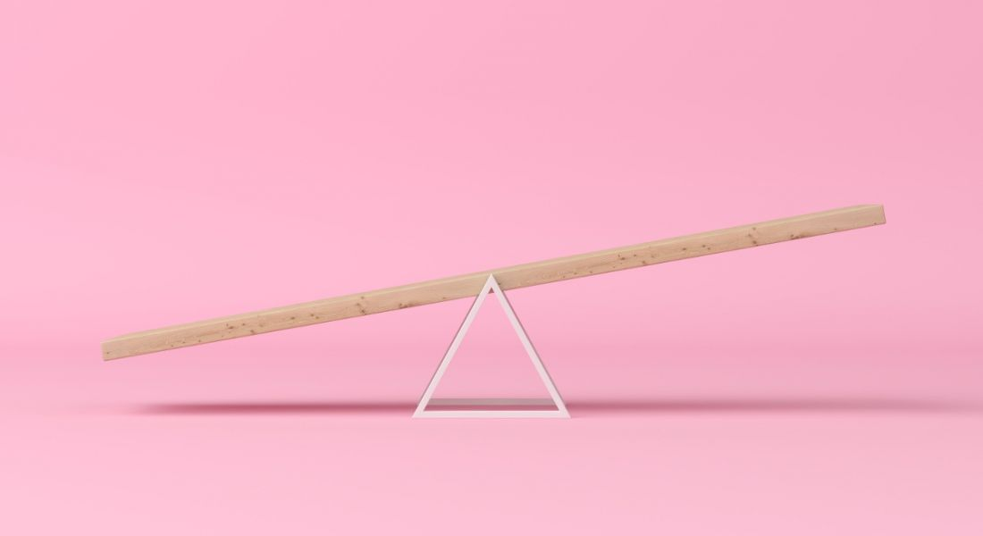 A wooden seesaw is balancing against a pink background, symbolising work-life balance.