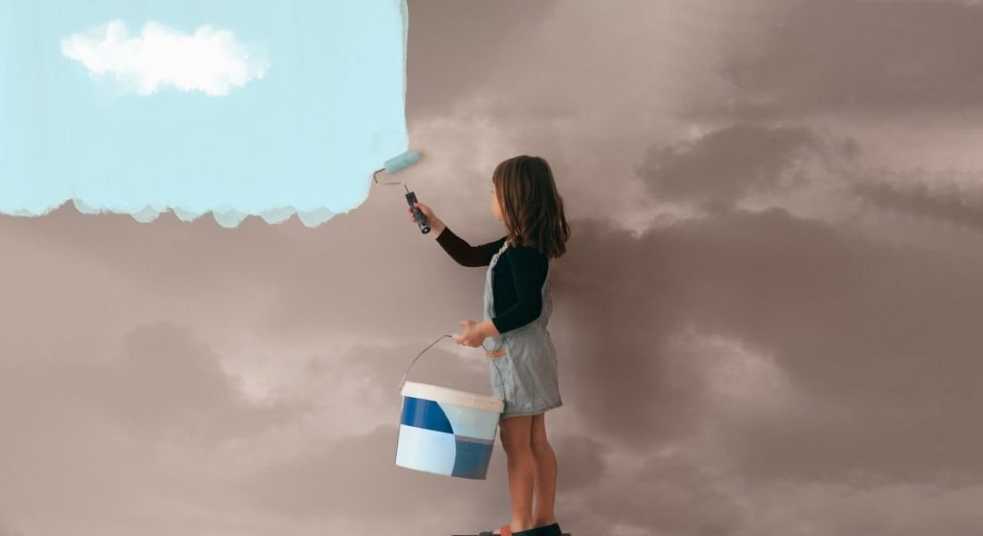 Little girl uses a can of paint to colour the wall of a room from cloudy grey to clear blue sky.