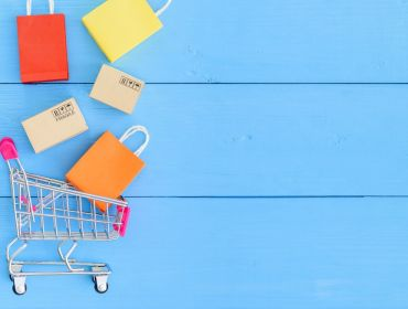 Colourful shopping bags are falling into a shopping trolley against a blue background, symbolising e-commerce and online shopping sites such as eShopWorld.