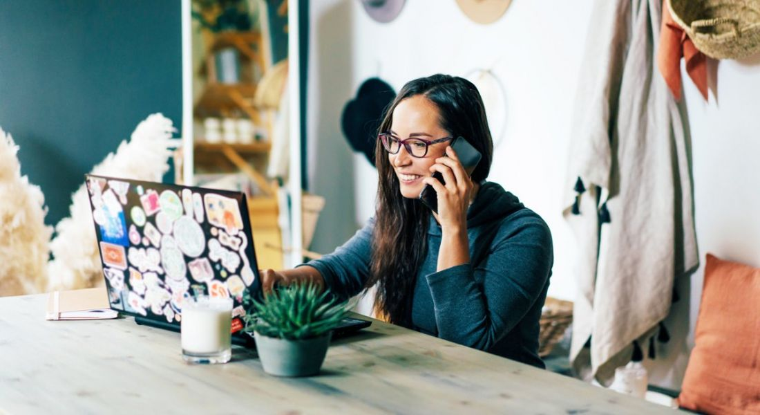 A woman wearing glasses is working remotely while talking on the phone and smiling.