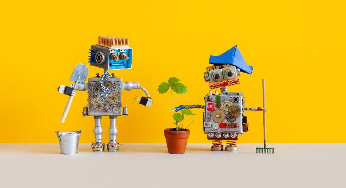 Two toy robots are staying connected and gardening together for their mental health against a yellow background.